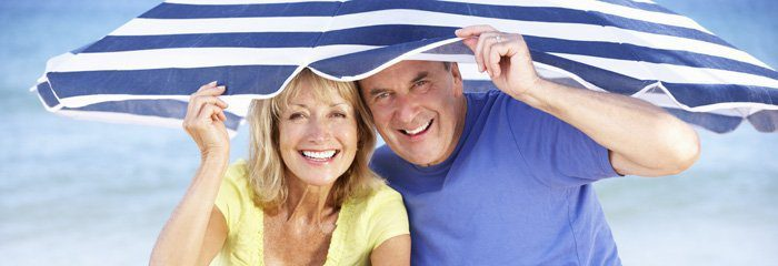 Senior Couple Sheltering From Sun Under Beach Umbrella